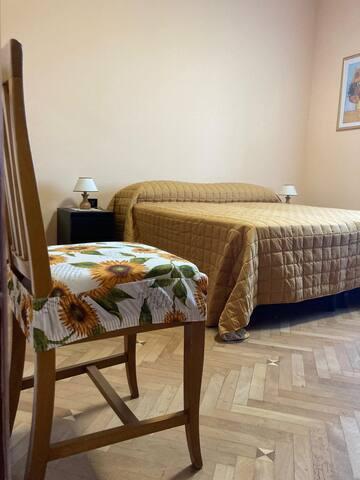 Camera matrimoniale, spaziosa, con ampio armadio, cassettiera e due comodini. Finestra con vista sulle splendide montagne della Val Grande. Pavimento in legno.