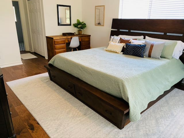 Downstairs owner's suite with private bathroom features new King sized Nectar mattress, Egyptian cotton bedding, smart TV, desk, private door to lovely patio with pond view.  All bedrooms have ceiling fans.