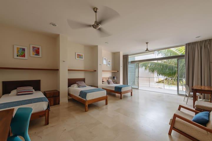Habitación 3, cuenta con 3 camas tamaño individual y 2 escritorios para trabajar o tomar clases en línea.  Tiene balcón con vista al mar