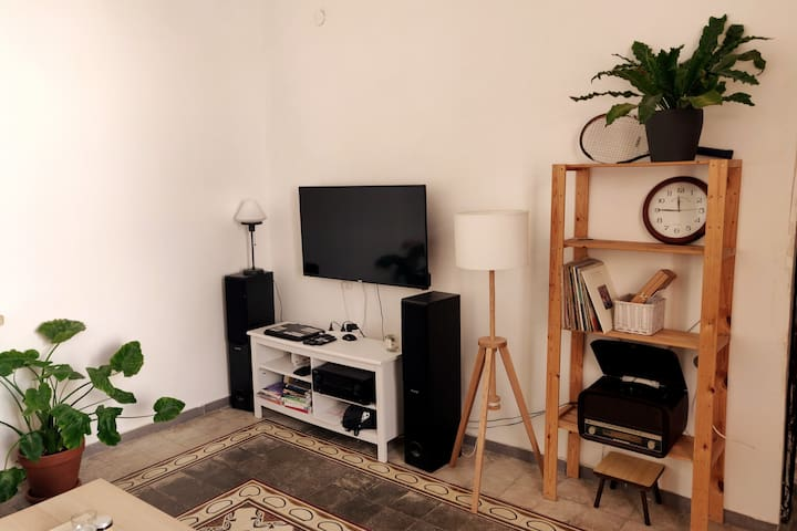 Living room entertainment system - a big screen TV, cables via streamer (which means Netflix is installed) and even a gramophone and a few records!