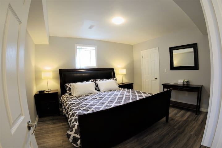 Spacious bedroom with king bed, alarm clock, closet with luggage racks and hangers.