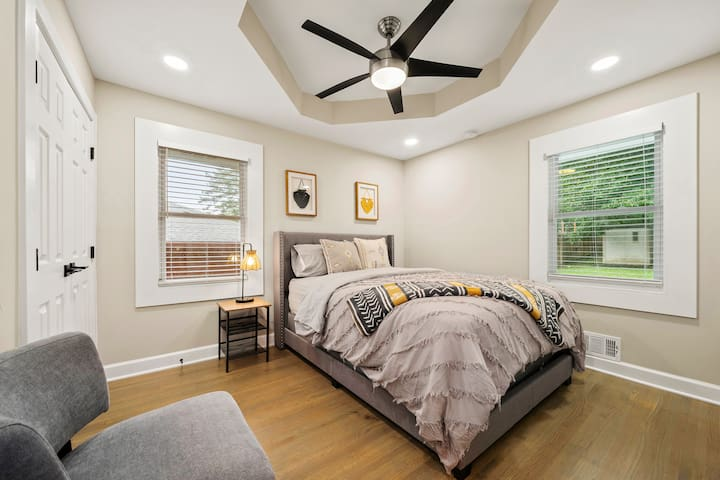 The spacious bedroom one with a large queen bed and a siting area