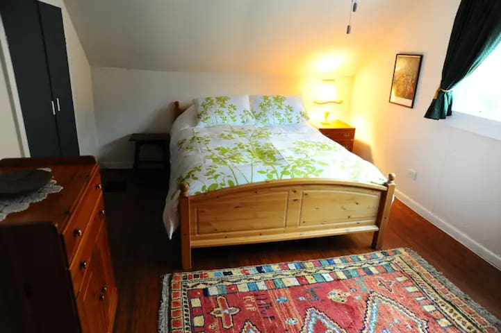 Queen sized bed with dresser, 2 bedside tables, armoire, and closet