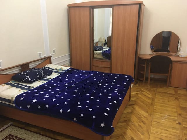 The spacious bedroom with a full-size bed.   - TV (upon request) - Bookshelf  - Closet  - Vanity table