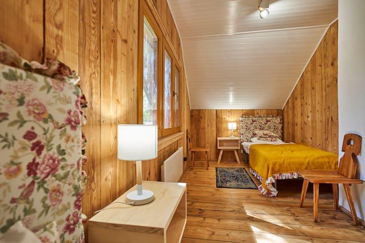 Sypialnia. Dwa pojedyncze łóżka z miłej, drewnianej przestrzeni.