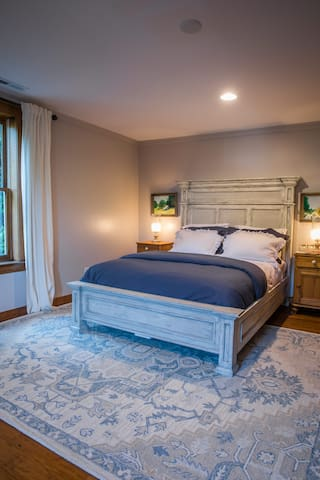 The Lenoir room is on the second floor and features a queen bed.  View of the woods and the front of the home.