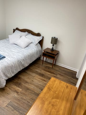 This room has a queen sized bed, night stand, and dresser. It has a large closet/dressing area attached. It can be accessed by the garage or from a hall that leads to the living room.