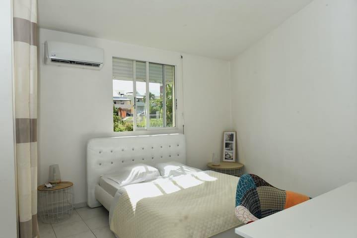 Une chambre privative très spacieuse avec vue sur jardin, disposant de la climatisation, dotée d'un bon lit douillet...