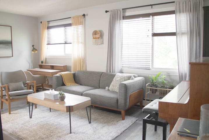 Living room, comfy and stylish sofa and armchair, a recently tuned piano, a dedicated workspace, and live plants to help you relax!