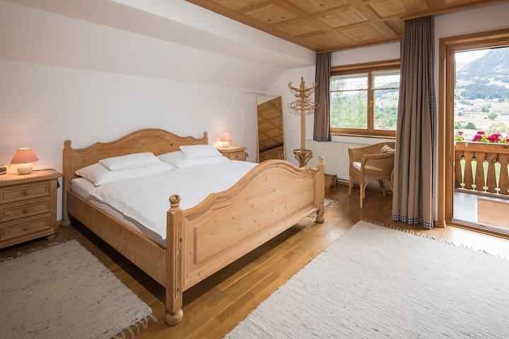 Spacious, sunny bedroom with direct access to balcony and bathroom.