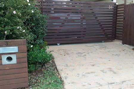 A sloping driveway leads to the narrow side gate on the right which is 570 mm wide.