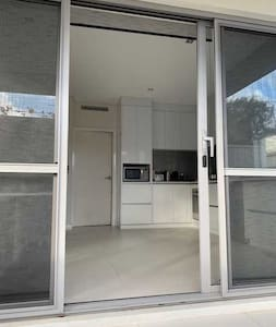 Entry is through wide patio doors , the single door width 105cm, there is a small rise of 6 cm and a further 3 cm to the door frame. Access is via a flat patio from a flat , 4m wide driveway.