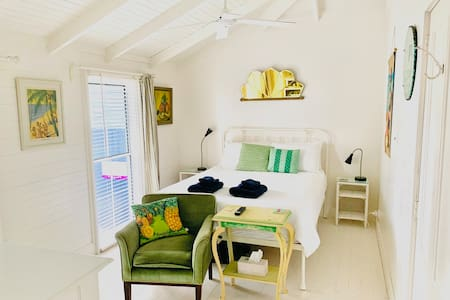 The light and airy Porch Room has a super comfy queen bed, bendy reading lamps, a high, raked ceiling, a ceiling fan, aircon and a  vintage beach vibe.