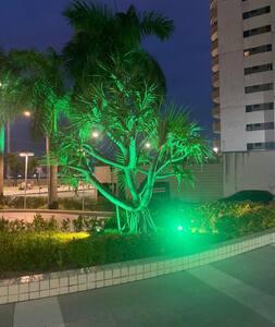 Rua particular que leva a entrada do prédio bem iluminada e sem obstáculos e degraus.
