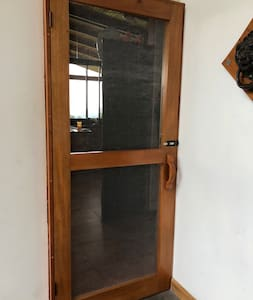 There is a screen door as well as a hand carved wood door.  The screen door has a lock latch to stay open while you unlock and enter the main house