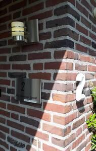 Er is verlichting bij de voordeur en er staat een lantaarnpaal voor het huis.
