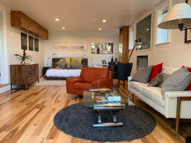 Luxuriate in a eurostyle suite with designer furnishings, eclectic art, Italian leather chair and sofa, dining table in front of electric fireplace, and natural wood platform bed.