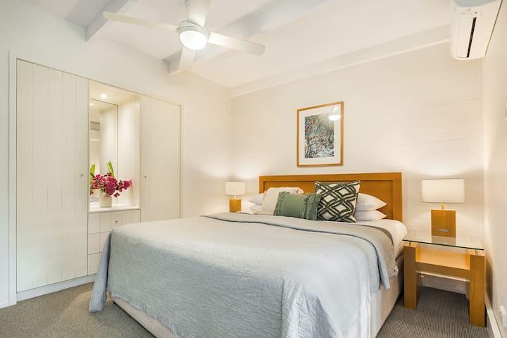 "Main Bedroom with King Bed, wardrobes, AC and 55""Smart TV / Soundbar on wall facing bed"