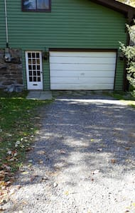 The driveway is flat, packed gravel. There are patio stones leading to the door.