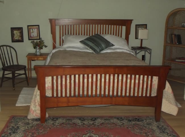 A queen sized bed facing the Dormer Window