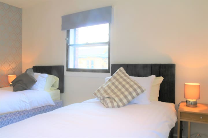 The twin room is the largest of the three bedrooms, a spacious L-shape with South and West facing windows.