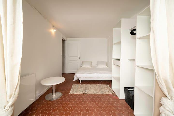 Chambre avec lit double et dressing et baie vitrée donnant sur le jardin