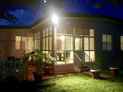 There are exterior lights illuminating the front and back of the house.