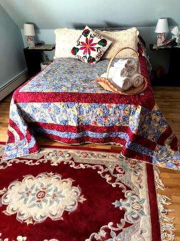 Guest bedroom. Handmade quilt and plenty of fresh towels in handmade basket.