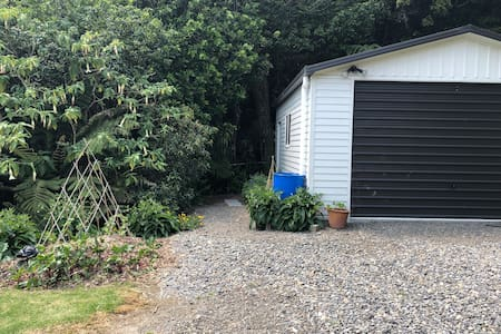 This is the parking area and the pathway to the cottage runs alongside, and behind the garage. It is not wide and the path would not be easy to negotiate in a wheelchair.