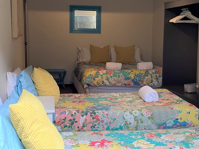 The downstairs bedroom with a queen bed and two single beds. There is a wardrobe, chest of draws and a TV.