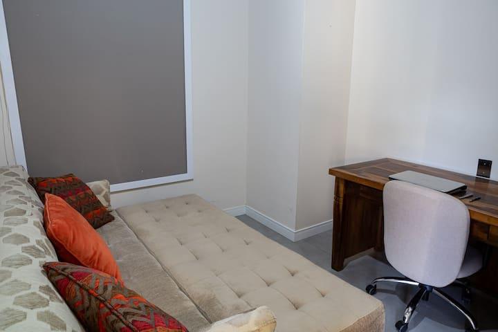 Quarto co sofá-cama e espaço para home office.