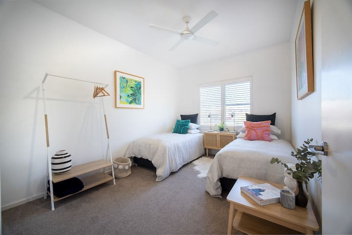 Twin Guest Room with oversizes down linen quilts, high quality linens and ample storage room with hanging clothes rack and ceiling fan for great air flow.