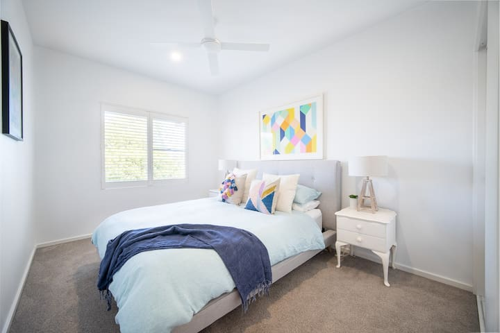 Queen bedroom with linen down quilt and high quality bedding, bedsides with storage, large built in robe, plus ceiling fan for great airflow.
