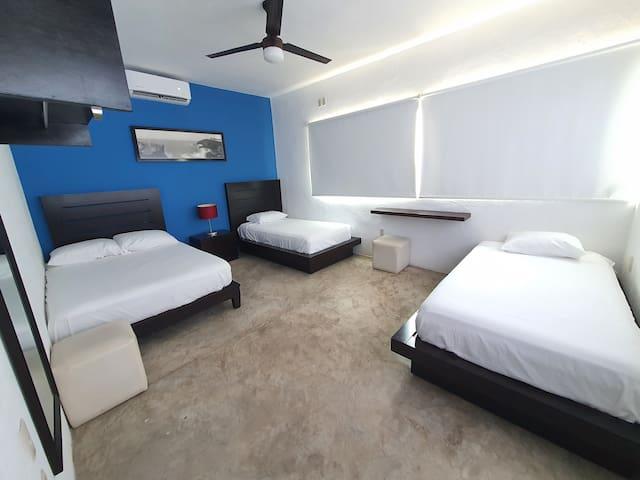 CAPRICHO - Recamara 1 : Son 3 camas ( 1 matrimonial y 2 individuales ) área de toallas  ( 1 por persona ) y cobijas ( 1 por cama ), ventilador, aire acondicionado, espejo, cuadro decorativo, persianas, cajonera-buro  y lampara de buro.