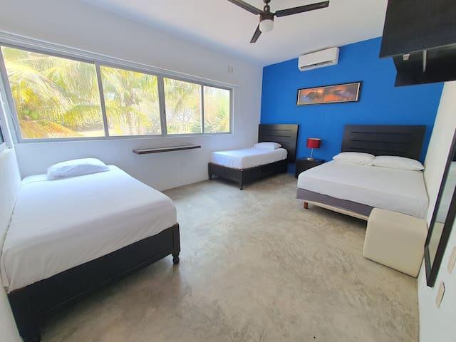 CAPRICHO - Recamara 2 : Son 3 camas ( 1 matrimonial y 2 individuales ) área de toallas  ( 1 por persona ) y cobijas ( 1 por cama ), ventilador, aire acondicionado, espejo, cuadro decorativo, persianas, cajonera-buro  y lampara de buro.