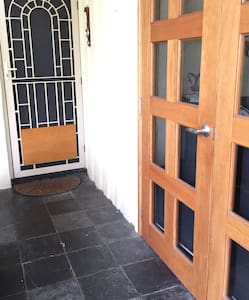 Flat entrance path to door through gate 81 cm wide