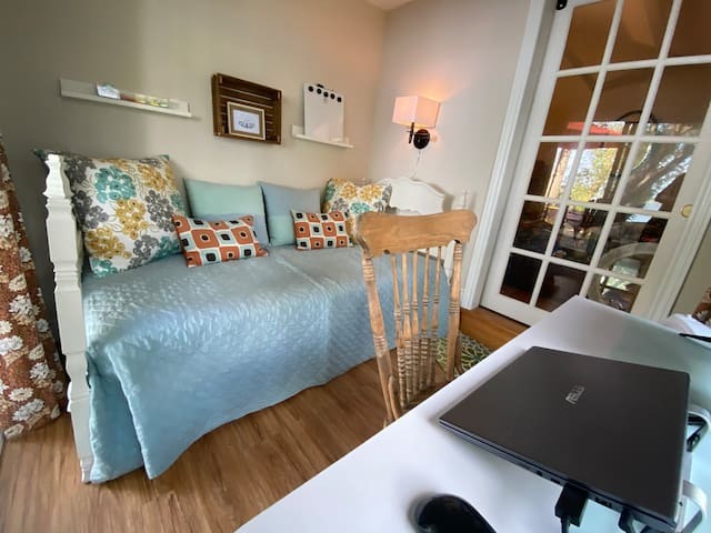 This twin bedroom adjoining the middle double room and separated by a glass barn door works hard too. There is a desk, white board, office supplies, and monitor.