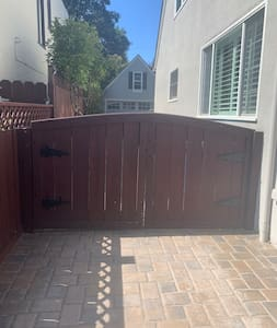 You can reach over gate to unlatch it. Then walk down driveway toward the casita.