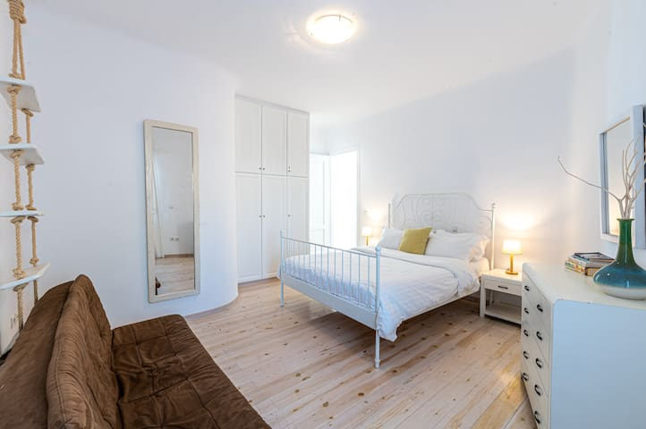 Bedroom with queen-sized bed and a cofy large sofa