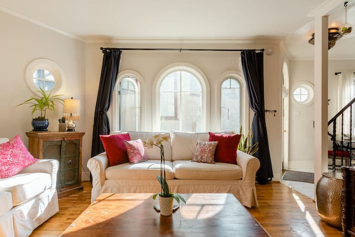 First Floor: There is no shortage of light in the guest house living room due to its 6 windows- all original dating back to the early 1920s. The arched and bulls eyes shapes are tell-tale signs.