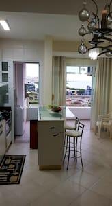 foto à partir da entrada do apartamento,  sala,  cozinha. Área plana.