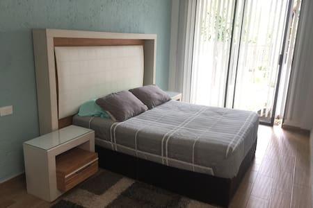 Espacio súper amplio alrededor de la cama queen size. Es una recámara bastante grande con mucho espacio.