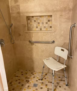 Easy step-in shower. Can fit wheelchair in shower. Has hand rails and shower sprayer nozzle.  All main doors in apartment are ADA width.