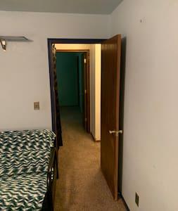 Looking from one bedroom through the door way to the other bedrooms doorway to the left is the wide hallway