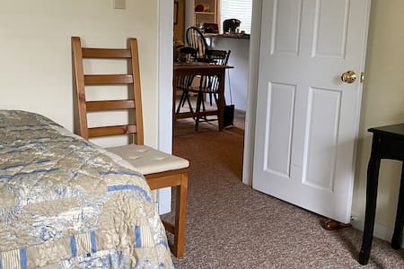 Twin bed bedroom entry into living room kitchen and bathroom