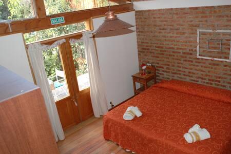 Dormitorio con salida a un patio privado, con amplia puerta de dos hojas, pisos al mismo nivel