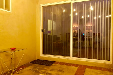 An exterior view of the spacious patio sliding door, which leads into the entertainment room. After enjoying a refreshment in the California sun, a short step provides access to the house.