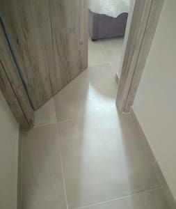 Flat tiling in the hall links every room,  bathroom,  both bedrooms and lounge kitchen - throughout the house.