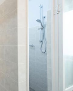 Our shower is fitted with a detachable shower head, which you can pop out of the holder and use as a hand shower.