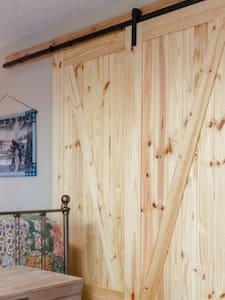 Wide sliding barn door entrance to bathroom.